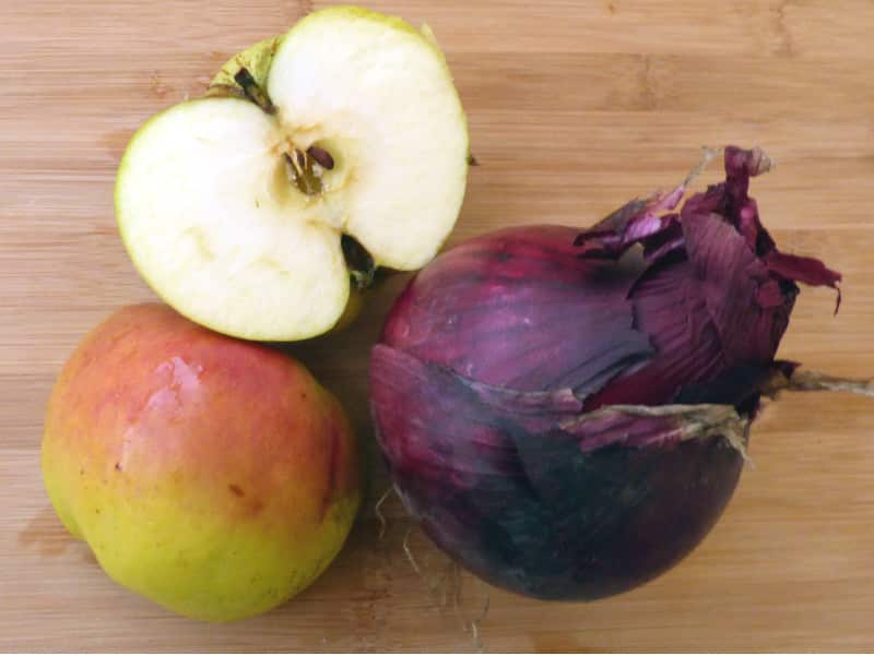 Apple, halved apple and red onion on chopping board