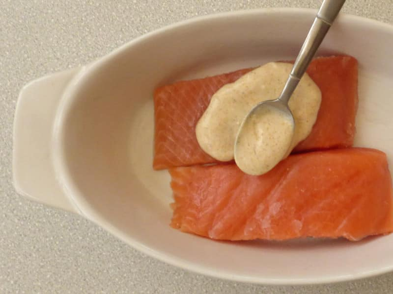 Dish of salmon fillets with spoon spreading spiced yogurt over