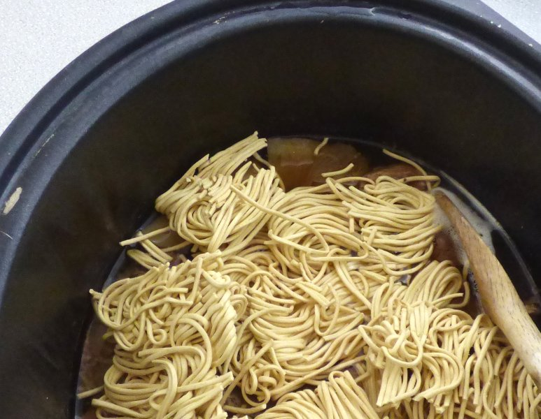 stirring noodles into slow cooker