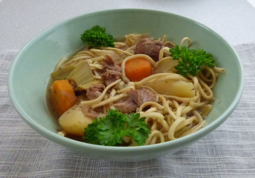 bowl of goat stew with noodles and parsley garnish