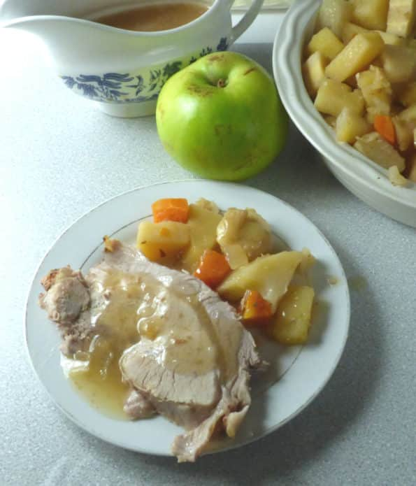 plate of pork, veg and sauce with apple, gravy boat and veg in the background