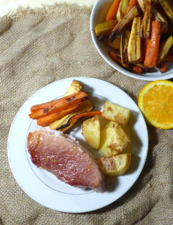 Gammon slices with vegetables and dish of veg in the background
