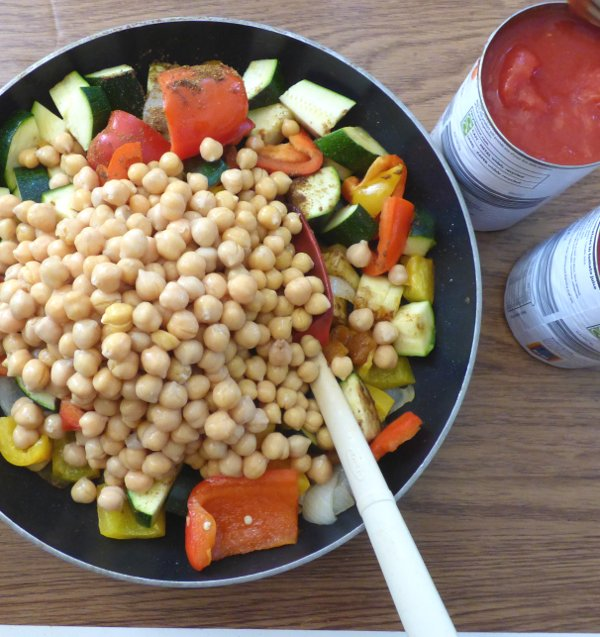 skilled of sauteed veg, spices and apricots with chickpeas piled on top and open cans of tomatoes to side