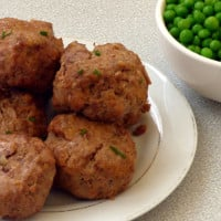 close up of plate of beef and cheddar meatballs with chive garnish, and side of peas