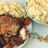 Slow cooker moroccan chicken on a plate with couscous, bowl of couscous to side