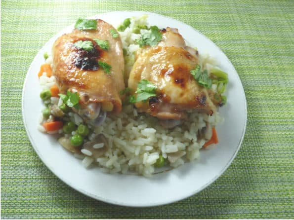 Plate of vegetable rice topped with honey lemon chicken thighs and chopped coriander/cilantro