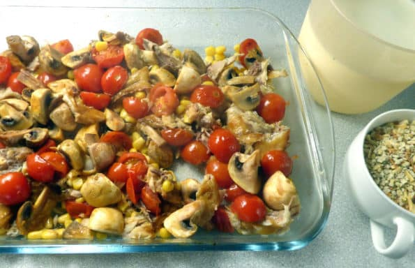 Ovenproof dish with cherry tomatoes, smoked mackerel chunks, sweetcorn, mushrooms, with jug of milk/cornstarch and cup of stuffing mix to one side