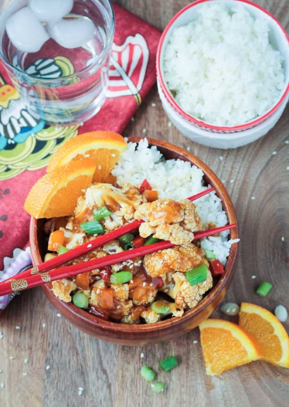 Bowl of orange cauliflower with chopsticks and a bowl of rice