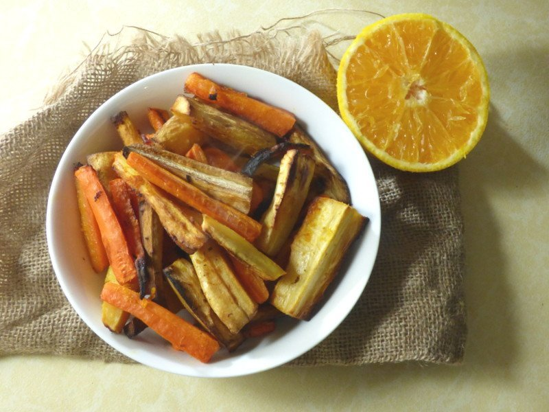Bowl of orange roast carrots and parsnips with orange to the side