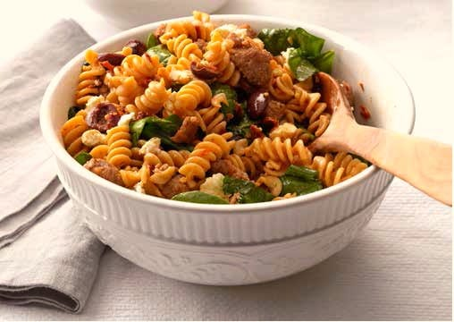 Bowl of Greek style pasta salad with wooden spoon