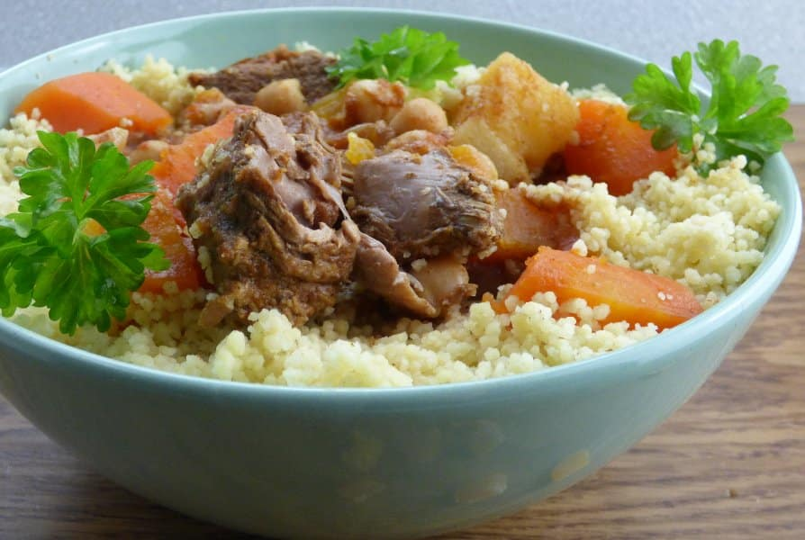 Bowl of tagine on bed of couscous, with parsley garnish