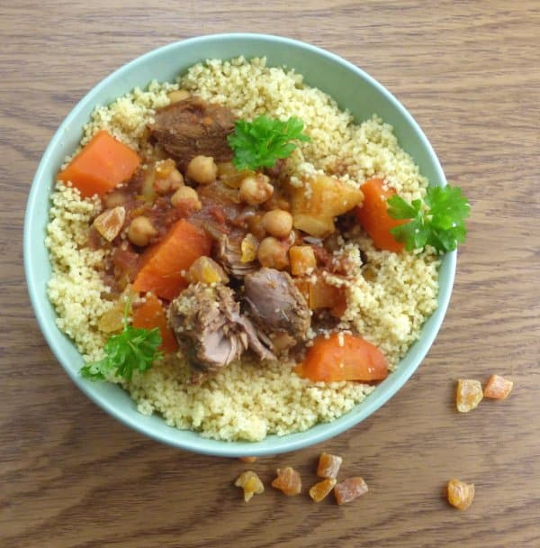overhead shot of lamb tagine on bed of couscous with parsley garnish, chopped dried apricots in foreground