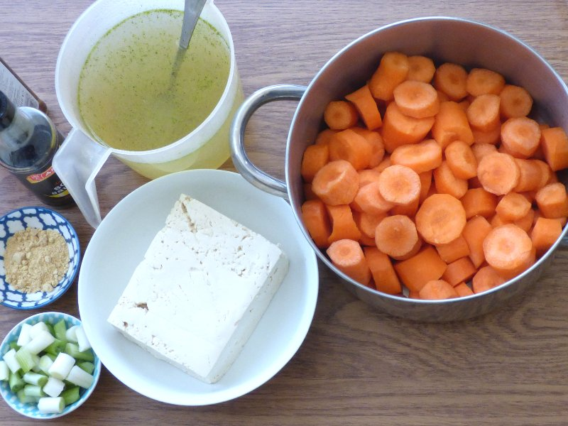 Ingredients for Carrot and Ginger Soup with Fried Tofu - bowl of sliced carrots, jug of stock, bowl of tofu, ground ginger and chopped scallions