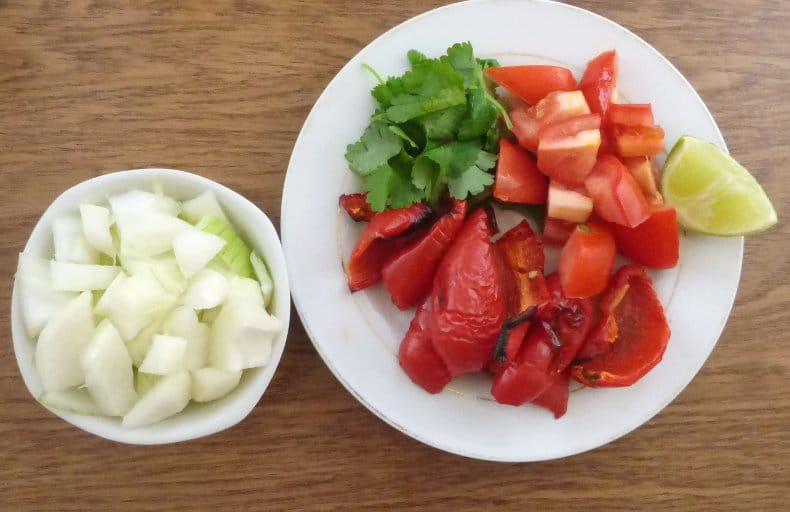 bowl of onion with lime juice, plate with lime wedge, coriander/cilantro, tomatoes and roasted red peppers set out separately
