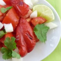plate piled with homemade salsa with roasted red peppers, on green napkin, with lime wedge