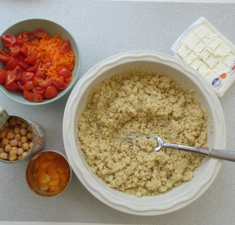 prepped couscous, feta cheese, tomatoes and carrots, open cans of chickpeas and orange segments