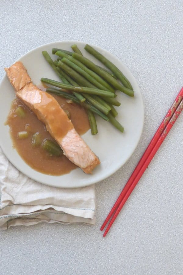plate with poached salmon with miso sauce and green beans, chopsticks to side