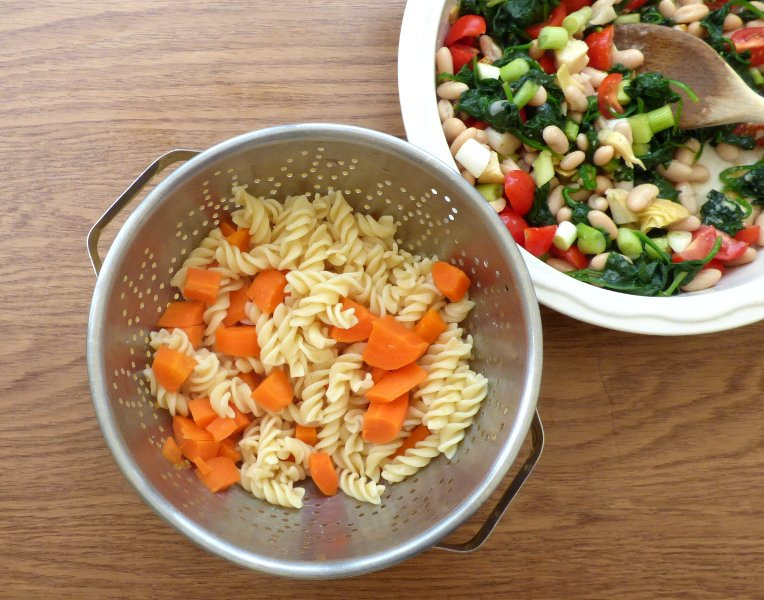 Colander of cooked pasta and carrots with serving bowl of other salad ingredients