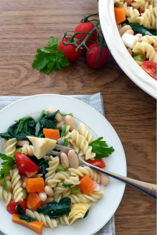Plate of tuscan pasta salad with serving bowl and cherry tomatoes