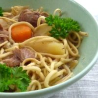 Bowl of mongolian spiced goat stew with noodles, parsley garnish