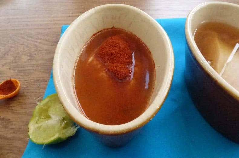 dishes with raw chicken, water and seasoning, one having paprika and lime, the other plain
