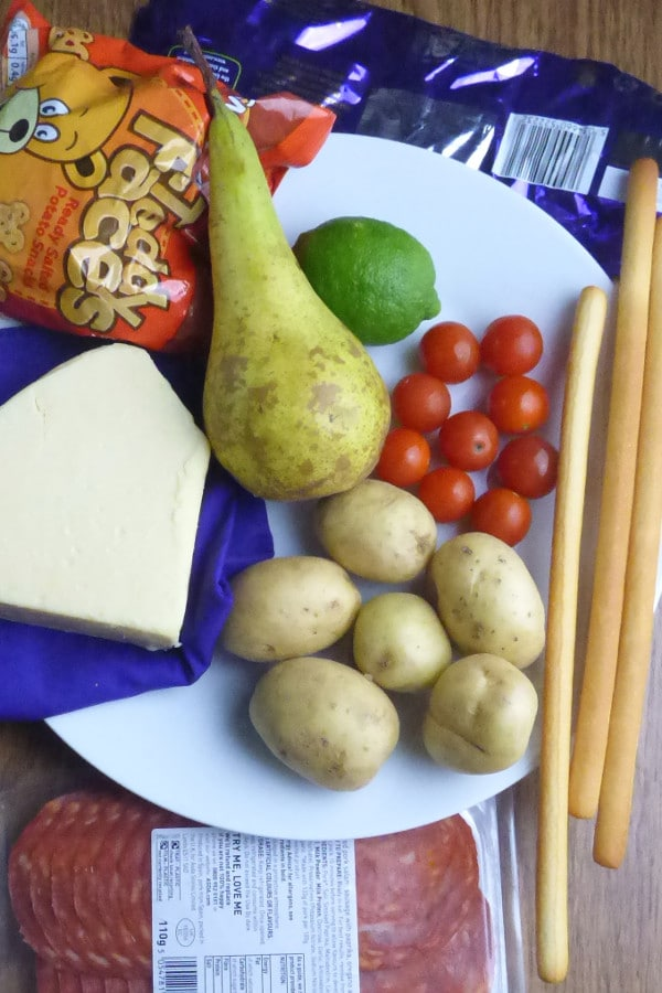 A plate with pear, lime, potatoes, cherry tomatoes, crisps adn cheese with chocolate and deli meat near by. All can be part of healthy recipes.