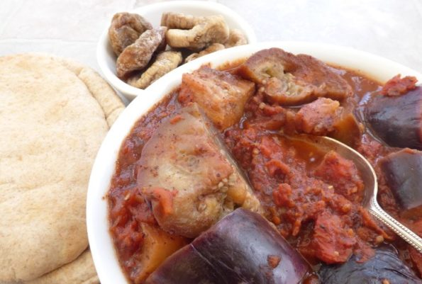 bowl of spicy aubergine in tomato sauce with pitta bread and dried figs in background