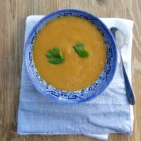 bowl of smooth lentil soup with carrot, with coriander garnish